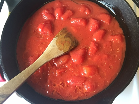 Whole peeled tomatoes in cast iron pan